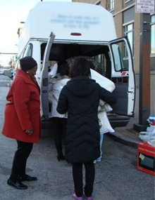 Merrick's staff members help load the Mattie B. Uzzle van.